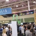 A picture from the 2018 LIFT conference. Showing people walking around the conference floor underneath the Vitalis show banner