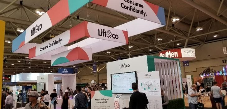 "A picture from the 2018 LIFT conference. Showing people walking around the conference floor. The ""Lift & Co"" signage is displayed above the people"